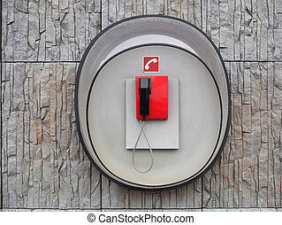 Image of red phone on wall of modern building