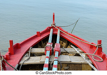 red wooden fishing boat anchored close-up