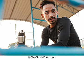 Image of relaxed african american man sitting at sports stadium outdoors