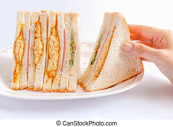 Sandwiches being picked up by woman's hand.