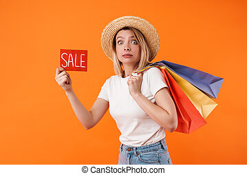 Image of scared woman holding shopping bags and sale banner