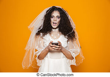 Image of scary zombie woman on halloween wearing wedding dress and holiday makeup using cell phone, isolated over yellow background