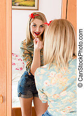 image of seductive young blonde pinup girl beautiful sexy woman having fun posing draws in the mirror red lipstick lips happy smiling and looking at camera portrait