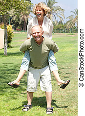 image of Senior man giving woman piggyback ride