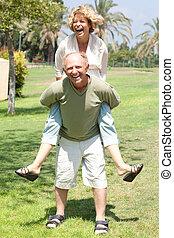 image of Senior man giving woman piggyback ride