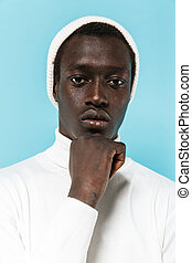Image of serious african american guy in white clothes looking at camera