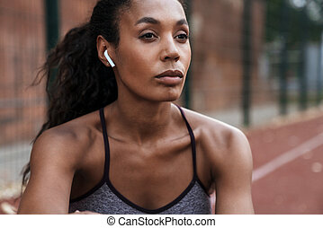 Image of serious african american woman with earbuds sitting at playground
