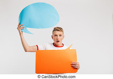 Image of shocked male student wearing basic t-shirt holding two commercial placards copyspace for your text, isolated over white background