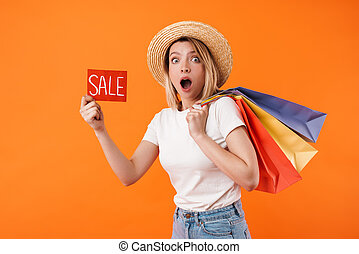 Image of shocked woman holding shopping bags and sale banner