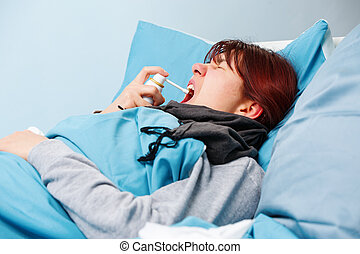 Image of sick brunette using throat spray lying in bed .