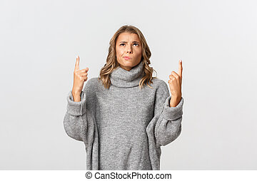 Image of skeptical blond girl in grey sweater, looking indecisive and pointing up, smirking doubtful, standing over white background