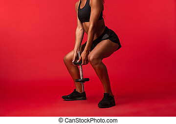 Image of skinny african american woman in black sportswear lifting dumbbell, isolated over red background