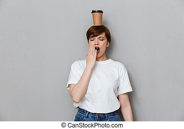 Image of sleepy woman yawning with takeaway coffee cup on her head