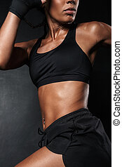 Image of slim african american woman in sportswear and hand wraps running