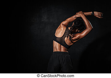 Image of slim african american woman in sportswear doing workout