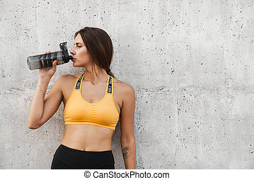 Image of slim woman in sportswear drinking water over concrete wall