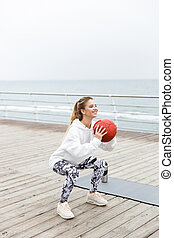 Image of smiling athletic woman doing exercises with fitness boll while working out near seaside