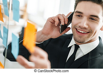Image of smiling businessman talking on cellphone while working