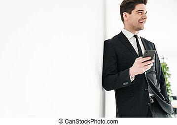 Image of smiling businessman wearing black suit using mobile phone