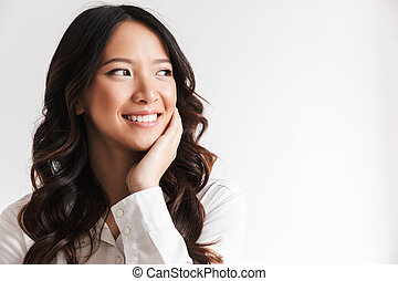 Image of smiling chinese woman with long dark hair looking aside at copyspace and touching cheek, isolated over white background in studio