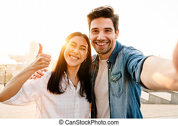 Image of smiling couple showing thumb up and taking selfie