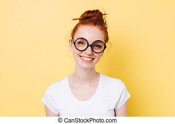 Image of smiling ginger woman in yeglasses looking at camera