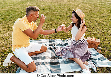 Image of smiling middle-aged man taking photo of nice woman on retro camera while sitting in park