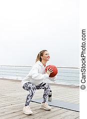 Image of smiling sporty woman doing exercises with fitness boll while working out near seaside