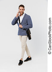 Image of smiling young man in jacket talking on cellphone while walking