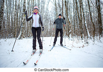 Image of sports woman and man skiing in winter forest