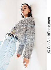 Image of stylish asian woman looking at camera while leaning on wall