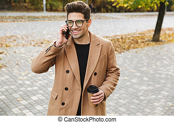 Image of stylish smiling man wearing coat talking on cellphone and drinking takeaway coffee in autumn park