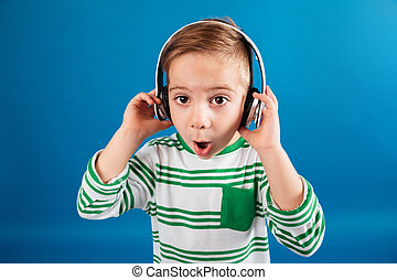 Image of Surprised young boy listening music by headphone