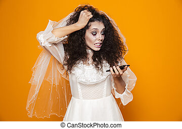 Image of surprised zombie woman on halloween wearing wedding dress and holiday makeup using cell phone, isolated over yellow background
