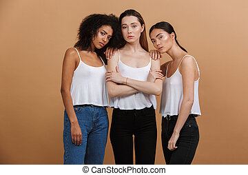 Image of three beautiful international women: caucasian, african american and asian girls in casual clothing, standing together isolated over beige background