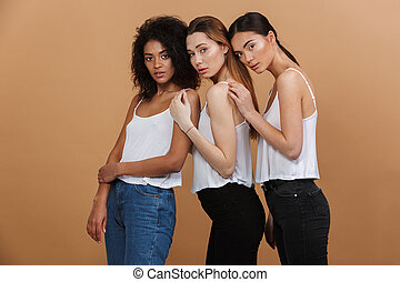 Image of three beautiful women of different nation: caucasian, african american and asian girls in basic clothing, standing together isolated over beige background