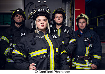 Image of three firemen men and woman on background of fire truck