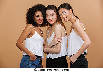 Image of three joyful smiling women of different nation: caucasian, african american and asian girls in jeans, standing together isolated over beige background