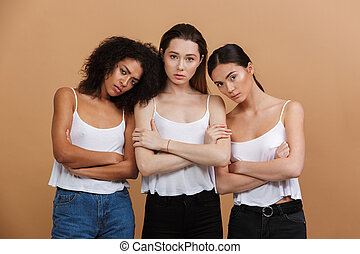 Image of three serious interracial women: caucasian, african american and asian girls in jeans, standing with arms crossed isolated over beige background