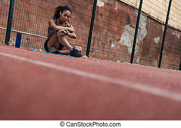 Image of tired african american woman with earbuds sitting at playground