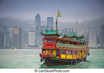 Image of traditional Chinese Junkboat sailing across Victoria Harbour in Hong Kong.