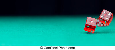 Image of two dice falling on green table