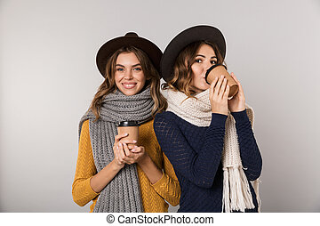 Image of two european women wearing hats and scarfs holding takeaway coffee in paper cups, isolated over gray background