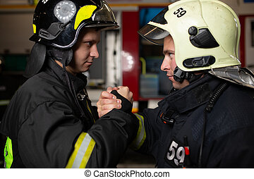 Image of two firemen wearing helmets waving their handshake