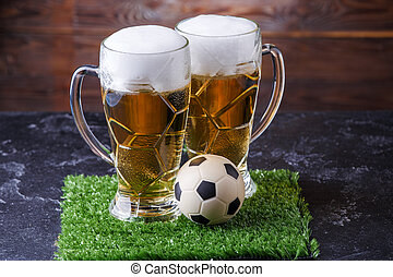 Image of two glasses of beer, soccer ball on green grass