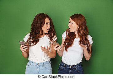 Image of two outraged women with red hair using cell phones ...