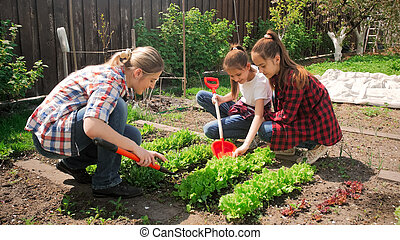 Image of two teenage girls with mother working in backyard garden