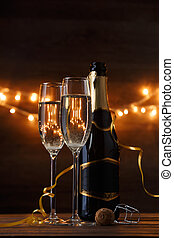 Image of two wine glasses with wine, bottles, cork, burning garland