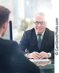 Image of two young businessmen using computer at meeting