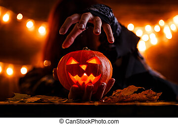 Image of witch with long hairs holding pumpkin